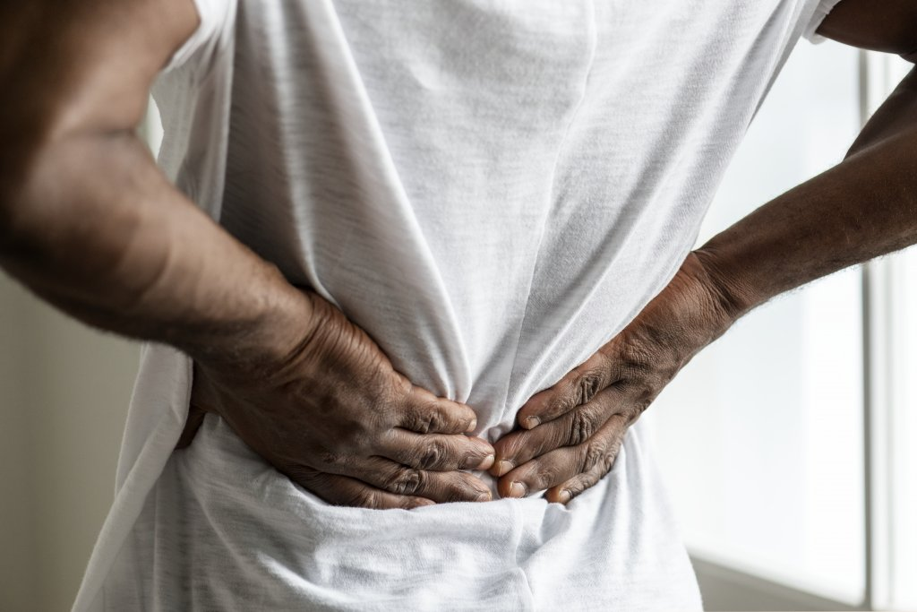 To show a man suffering back pain from a pre-existing injury
