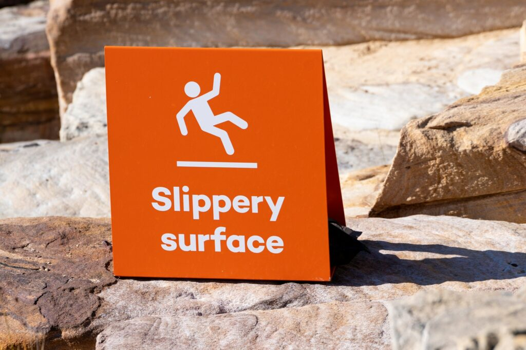 Sign showing warning of caution that rocks are slippery when wet.